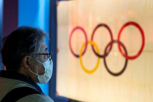 Un ciudadano japonés pasa ante los cinco aros olímpicos, en Tokio.