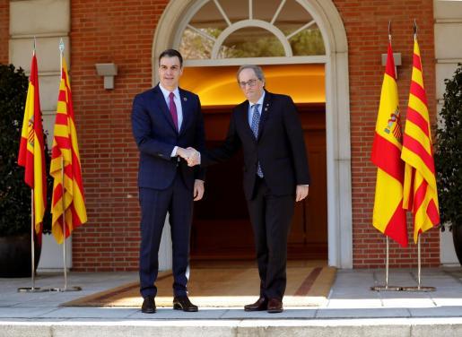 El presidente del Gobierno, Pedro Sánchez y el president de la Generalitat de Cataluña, Quim Torra, se saludan momentos antes de afrontar la primera reunión de la mesa de diálogo este miércoles en el Palacio de La Moncloa.