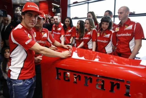 Los pilotos españoles de Ferrari, Fernando Alonso (i) y Marc Gené, firman en el mostrador de una tienda de la escudería italiana.