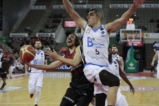 El jugador del Covirán Granada Josep Pérez intenta encestar ante la oposición del capitán del B the travel brand Mallorca Palma, Carles Bivià, durante el partido disputado en el Palacio de los Deportes de Granada con victoria de los locales 68-67.