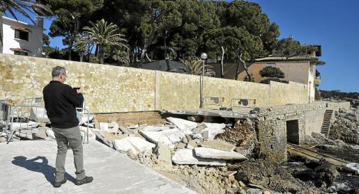 Un turista hace una foto de los daños en el paseo de Cala Gat.