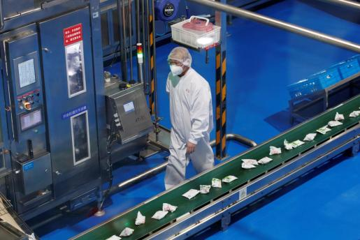 Un trabajador se cubre con una mascarilla.