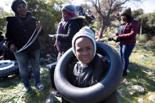 Un niño africano juega con una rueda en la localidad turca de Canakkale este martes antes de que su familia se lance al mar Egeo con rumbo a la isla de Lesbos (Grecia).