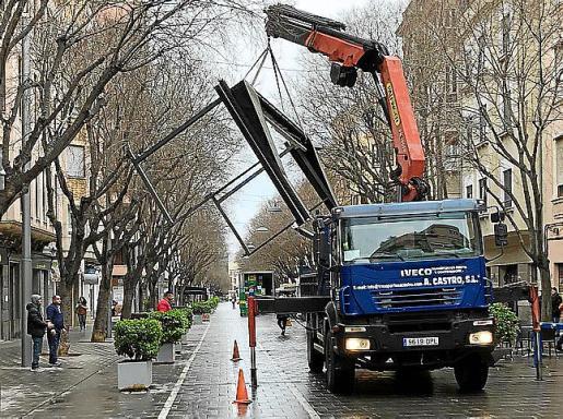Una grúa procede a llevarse la estructura del cerramiento de una terraza en Blanquerna.