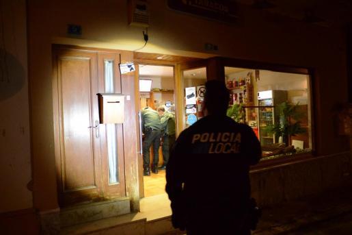 Un policía local alumbra con una linterna la entrada del estanco asaltado.