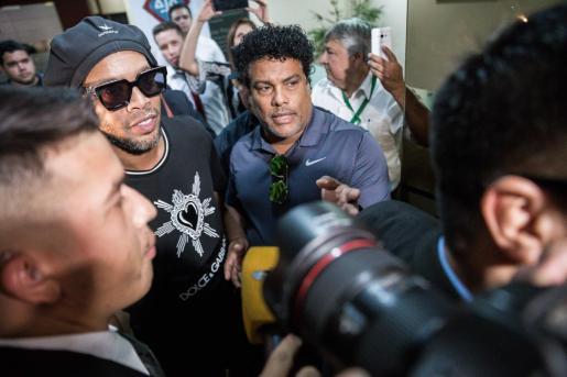El exjugador de fútbol brasileño Ronaldinho Gaúcho (i) y su hermano, el empresario Roberto de Assis Moreira (d), son rodeados por miembros de la prensa tras declarar ante la Unidad Especializada en la Lucha contra el Crimen Organizado de la Fiscalía General del Estado este jueves, en Asunción.