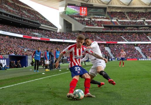 El defensor inglés Kieran Trippier, del Atlético de Madrid, disputa el balón con el delantero marroquí Youssef En-Nesyri del Sevilla, durante el partido correspondiente a la jornada 27 de LaLiga Santander disputado este sábado en el Estadio Wanda Metropolitano en Madrid.