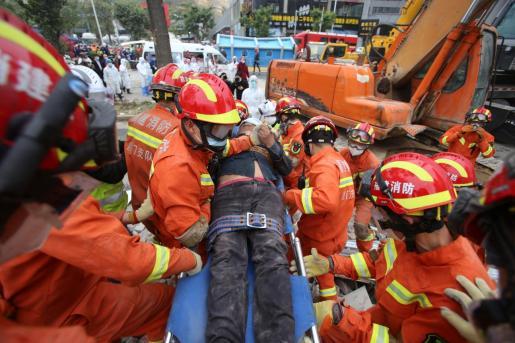 Los equipos de rescate de China sacan a los heridos tras derrumbarse el hotel.