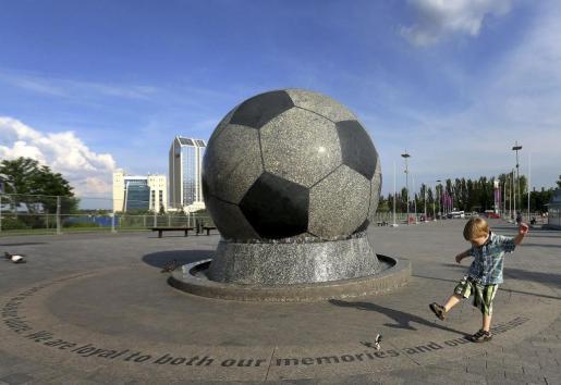 Un niño ucraniano juega delante de una fuente con forma de balón de fútbol frente al estadio Donbass Arena de Donetsk, Ucrania.