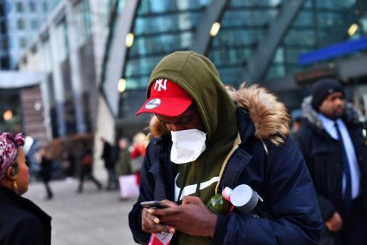 Un joven se cubre la boca con una mascarilla en una calle de Londres.