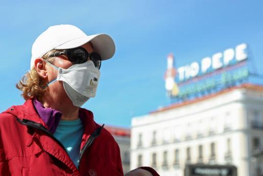 Una mujer con mascarilla en la Puerta del Sol.