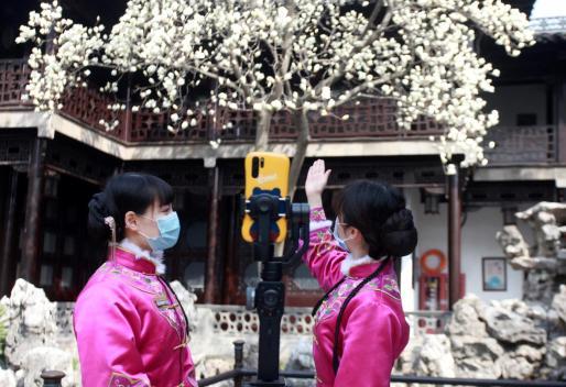 Dos guías turísticas con mascarilla en Yangzhou.