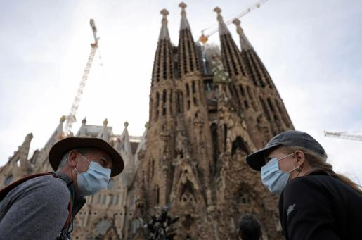 Tourists wear protective face masks as they talk in front of landmark Sagrada Familia basilica, which will stop receiving visitors and suspend its construction work starting from Friday as a precautionary measure due to the coronavirus outbreak in Barcelona, Spain March 12, 2020. REUTERS/Nacho Doce HEALTH-CORONAVIRUS/SPAIN-SAGRADA FAMILIA