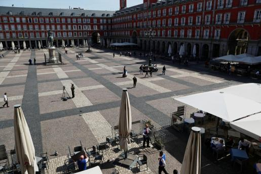 Trabajadores retirando este viernes las terrazas de la emblemática Plaza Mayor de Madrid.
