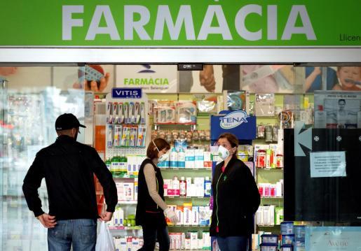 Varias personas se acercan a una farmacia en Barcelona, este sábado.