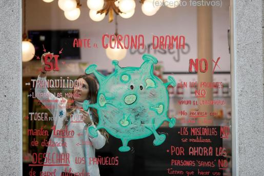 Noelia, trabajadora y autora de la obra gráfica de la farmacia La Salud de Lugo, situada en la Rúa do Teatro, ha causado gran expectación este jueves con su escaparate cuyo leit motiv es el coronavirus.