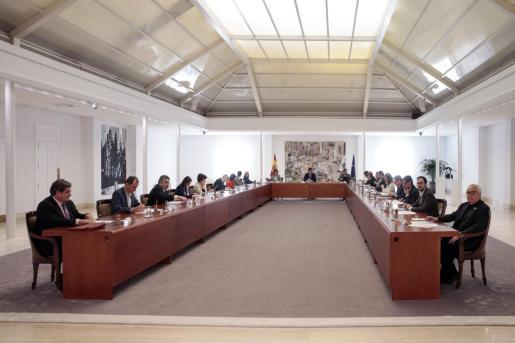Fotografía facilitada por la Moncloa que muestra al presidente del Gobierno, Pedro Sánchez (c), que preside la reunión de Consejo de Ministros, en el Palacio de la Monclo a en Madrid, este sábado, para aprobar el decreto que declara el estado de alarma.