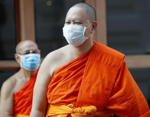 Varios monjes budistas pasean con mascarillas por las calles de Bangkok.