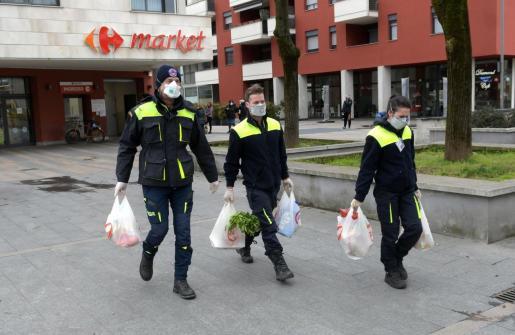 Los voluntarios de Protección Civil entregan alimentos y medicinas en los hogares a las personas que no pueden salir en Italia.