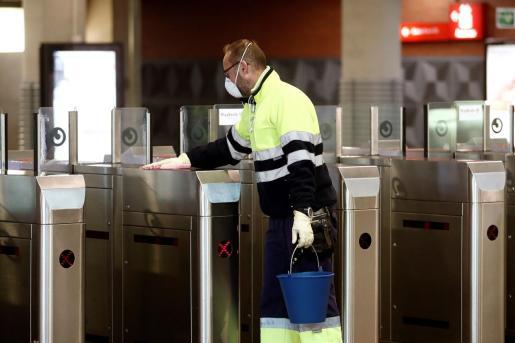 Un operario de limpieza desinfecta los tornos de acceso a la estación de cercaniás de Atocha Renfe, en Madrid.