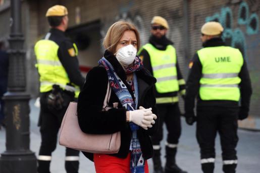 Una mujer camina con una mascarilla junto a miembros de la UME en la calle Carretas en Madrid este lunes.
