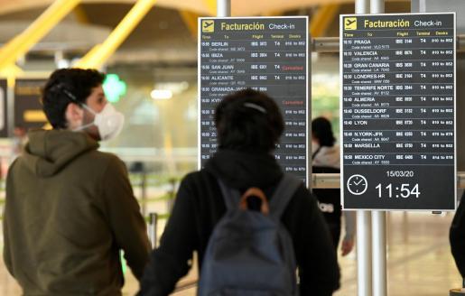 GRAF7121. MADRID, 15/03/2020.- Pasajeros se protegen con mascarillas en la terminal 4 del aeropuerto Adolfo Suarez Madrid Barajas, este domingo. EFE/ Víctor Lerena Situación en el aeropuerto de Barajas