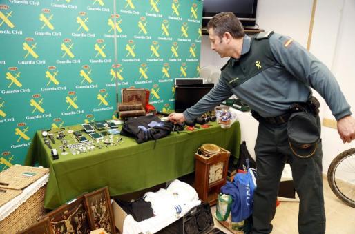 Un cabo de la Guardia Civil muestra los objetos recuperados.