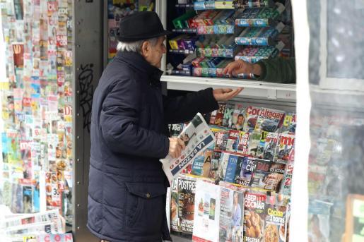 Un hombre compra un periódico este martes en un quiosco de Madrid.