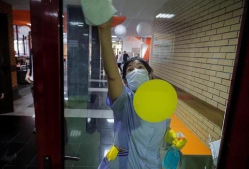 Una mujer, con mascarilla, haciendo labores de limpieza en un hospital. e