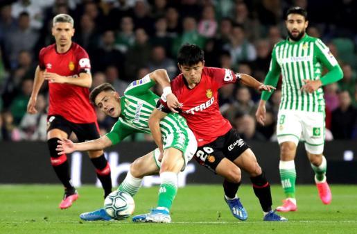 El centrocampista del Real Betis Álex Moreno (i) disputa un balón con Takefusa Kubo, centrocampista japonés del Mallorca, durante el partido de Liga en Primera División disputado en Benito Villamarín.