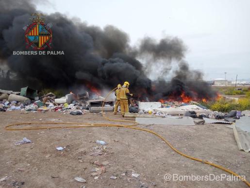 Imagen de dos bomberos sofocando el incendio de basura que se ha producido este miércoles por la mañana en las inmediaciones de Son Banya.