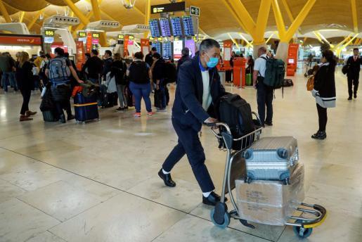 Viajeros protegidos con mascarillas en el aeropuerto Madrid-Barajas Adolfo Suárez como prevención al coronavirus.