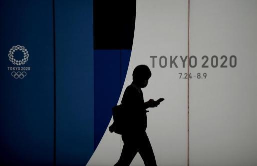 Un ciudadano de Tokio pasa ante un cartel anunciador de los próximos Juegos Olímpicos.