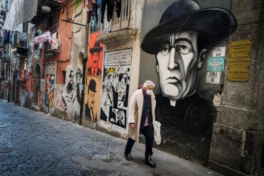 Una con mascarilla por una calle de Nápoles.