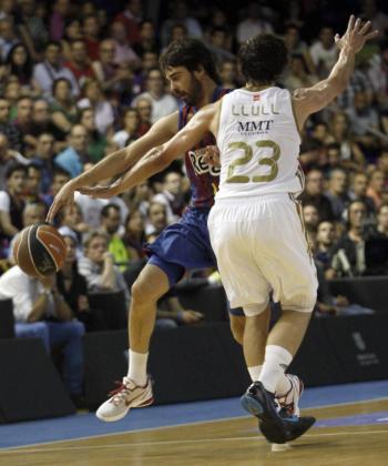 El jugador del Barça Regal, el escolta Juan Carlos Navarro (i) lucha con el base-escolta Sergi Llull (d), del Real Madrid.