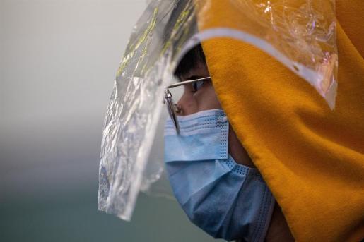 Una ciudadana china se cubre el rostro con varios materiales de protección.