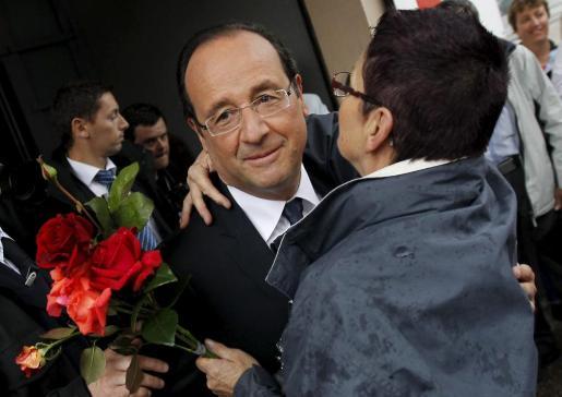 El presidente francés, François Hollande, saludado por una de sus partidarias al acudir ayer a su colegio electoral.