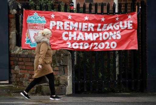 Una mujer pasea por delante de una pancarta en la que se celebra el virtual campeonato liguero del Liverpool tras detenerse la competición en la Premier League.