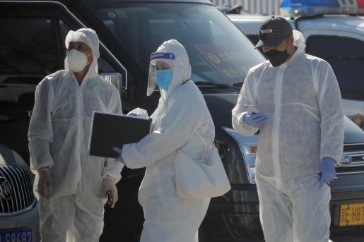 Trabajadores con el uniforme para protegerse del coronavirus en China.