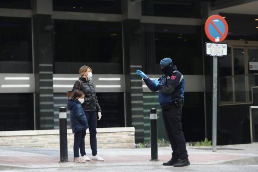 Un policía, alertando a una mujer y su hija.