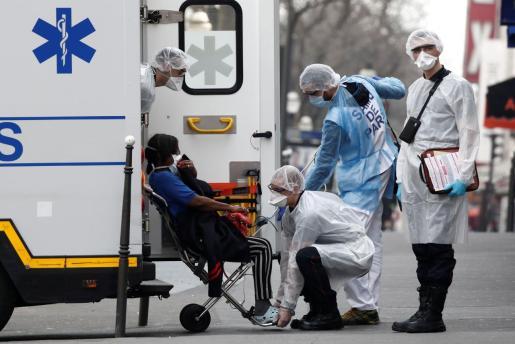 Profesionales sanitarios evacuan a un enfermo con coronavirus en Francia.