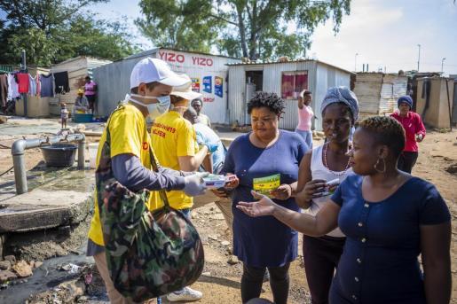 Un voluntario reparte jabón y folletos en un suburbio de Johannesburgo.