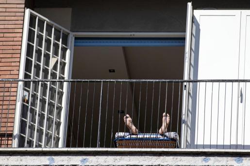 Un vecino de Roma pone sus pies al sol en su vivienda de la calle Francesco Acri este sábado, cuando las cifras de víctimas mortales por el coronavirus han batido un nuevo récord.
