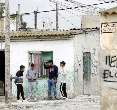 Un grupo de jóvenes, uno de ellos con mascarilla, en el poblado.
