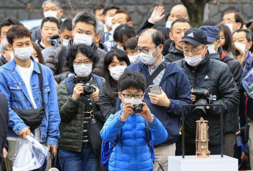 Ciudadanos de Sendai luciendo máscaras hacen fotos a la llama olímpica.