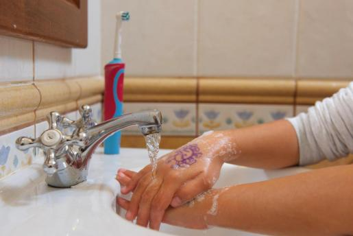 Imagen de una niña lavándose las manos.