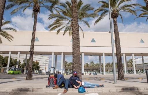 Varios turistas esperan a las puertas del aeropuerto de Palma.
