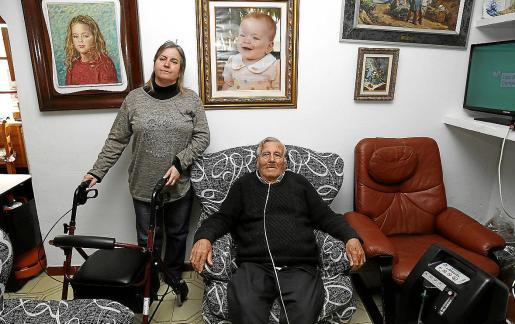 Manolo García, sentado en el comedor de su casa con respiración asistida, junto a su hija.
