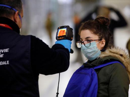 Un agente comprueba la temperatura a una ciudadana en Milán.