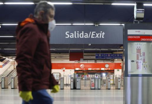 Un usuario de Cercanías Renfe protegido con guantes y mascarilla en el intercambiador de transportes de Nuevos Ministerios, en Madrid.